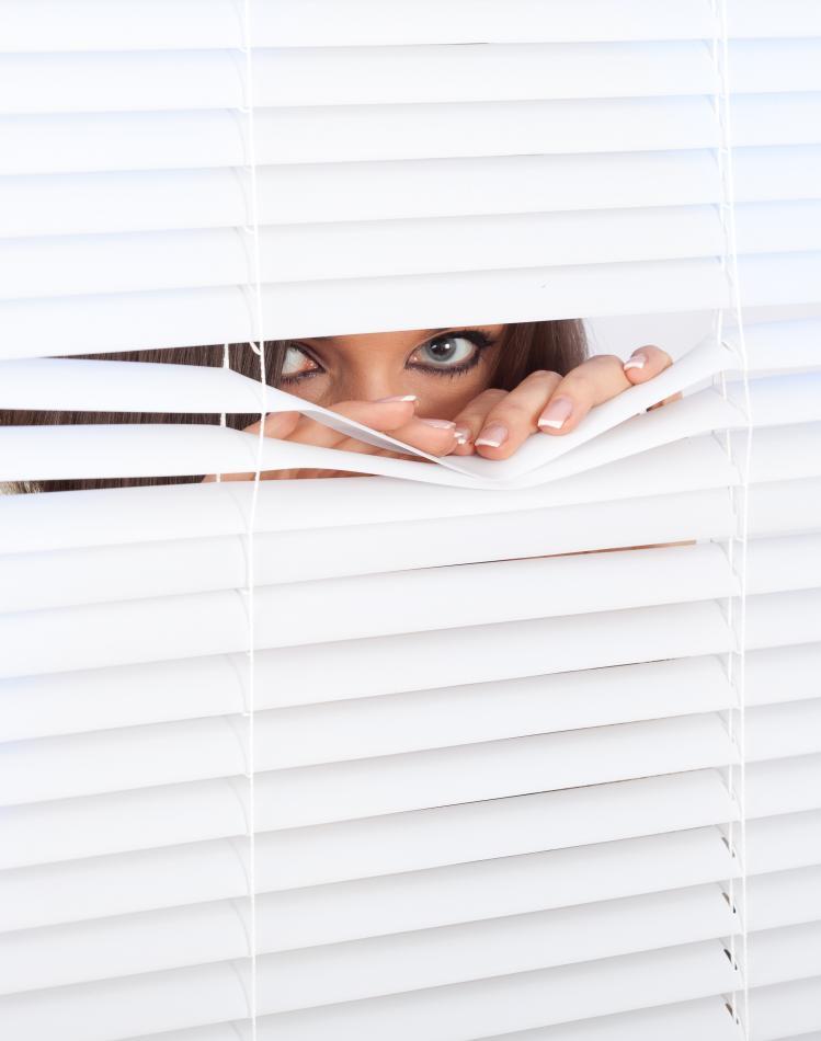 woman-peeking-through-window-blinds