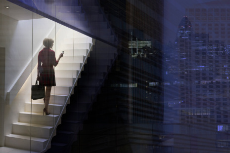 Business woman using mobile in the city at dusk